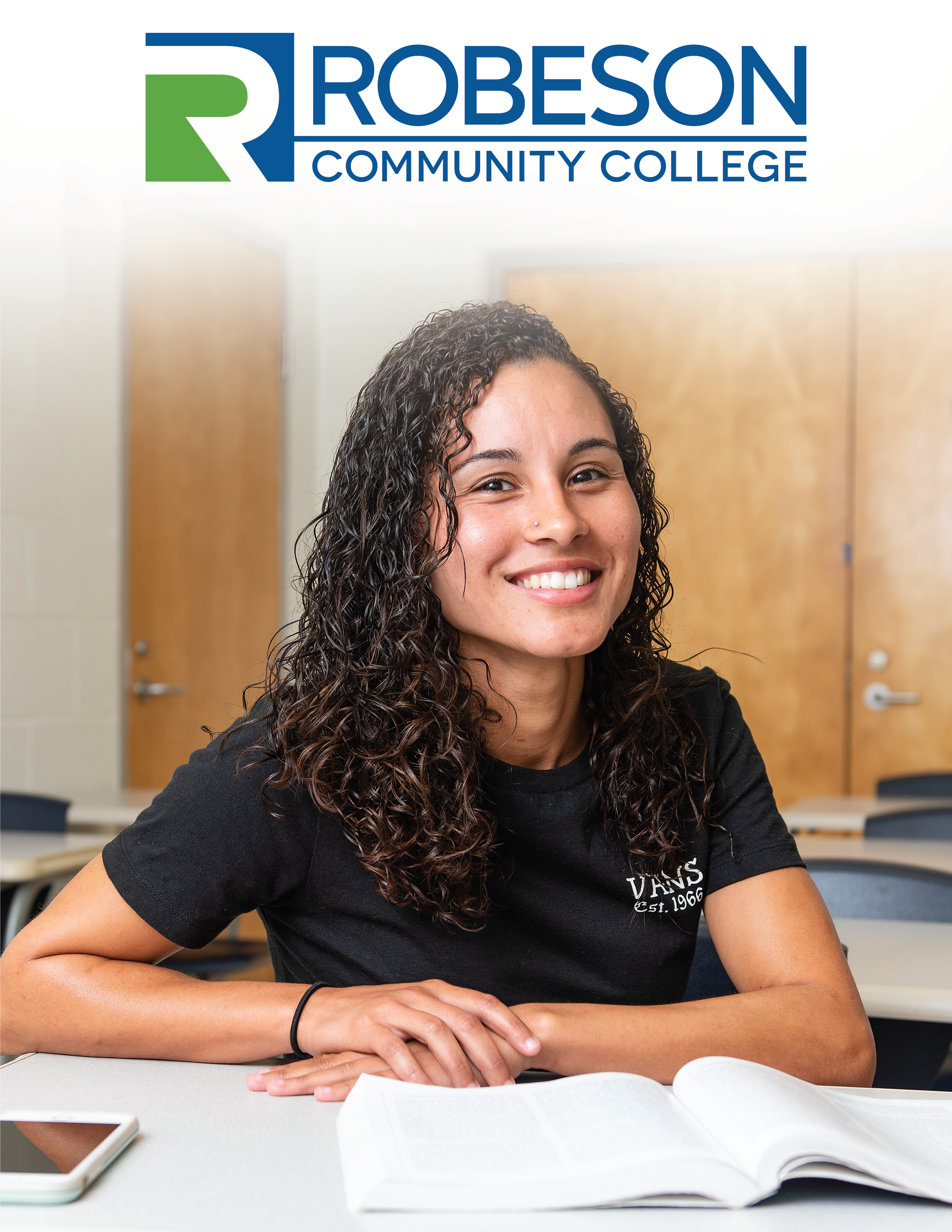 "Robeson Community College Logo with printed text ""2019-2020 Academic Catalog and Student Handbook"" and image of a young, smiling female at a desk with an open text book."